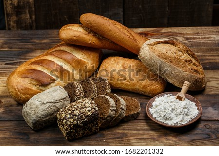 Different loaves of bread cooked with flour and gluten-free wheat on a wooden table #1682201332