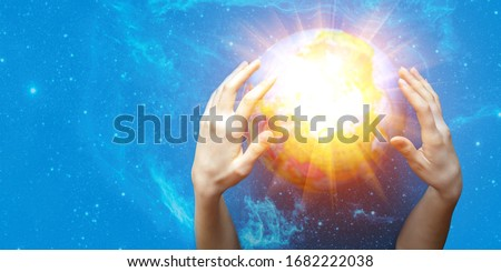 Two women's hands conjure a glowing ball on a blue starry background. The concept of paranormal abilities, clairvoyance, mysticism, divination. Elements of this image are provided by NASA. Banner Royalty-Free Stock Photo #1682222038