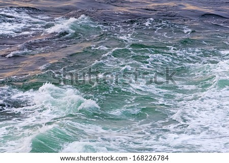 Green water and white foam of the north Atlantic ocean. Royalty-Free Stock Photo #168226784
