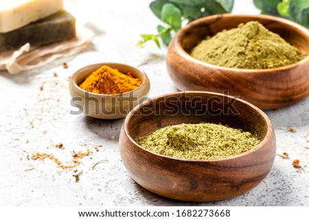 Ayurvedic hair care products. Henna, turmeric and neem powder in bowls on a grey background. Natural care and hair coloring.