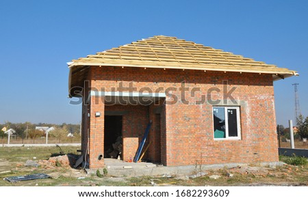 Building a simple brick house with incomplete hip, bonnet roof on the stage of framing from wooden trusses, roof beams.  #1682293609