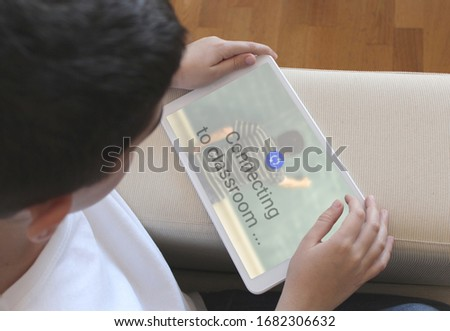 Concept for homeschooling, education, school at home, Kid connecting from home to a distance course with his tablet #1682306632