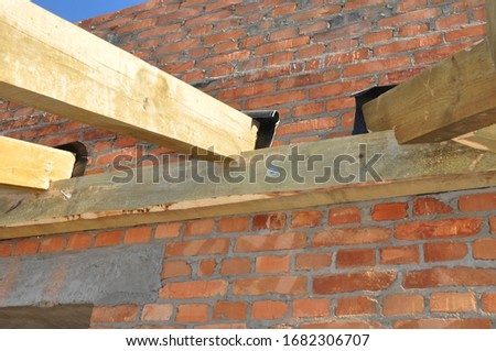 Construction and installation of the roof frame from wooden roof beams, trusses on the brick house. #1682306707