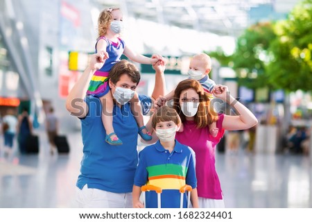 Family in airport in face mask. Virus outbreak. Coronavirus and flu pandemic. Safe travel with young child and baby. Mother, father and kids boarding airplane in surgical masks. #1682324401