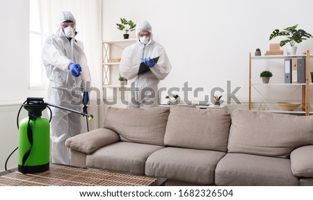Men in virus protective suit making treatment of sofas and surfaces from coronavirus, preventive measures, copy space Royalty-Free Stock Photo #1682326504