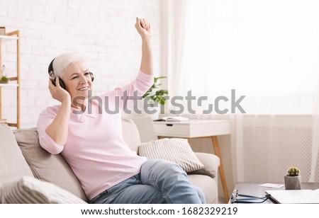 Quarantine can be fun. Joyful senior lady enjoying music in new headset at home, empty space #1682329219