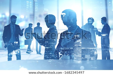 Silhouettes of diverse business people working together in blurry office with double exposure of night cityscape. Concept of partnership and teamwork. Toned image #1682345497