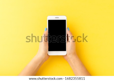 Overhead shot of woman's hands holding mobile phone with empty screen on yellow background. Top view