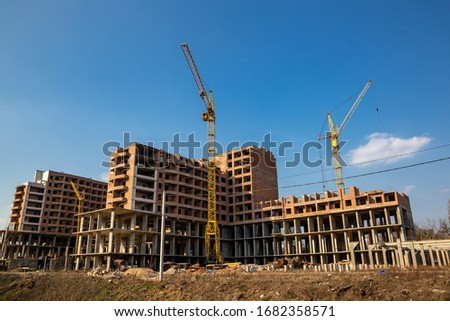 Work in progress on a new apartment block. Tall building under construction with cranes. Construction Site of New Building #1682358571
