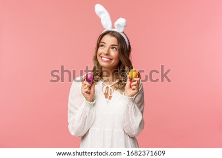Holidays, spring and party concept. Portrait of dreamy, tender young blond girl feeling happy, celebrating religious day, holy Easter, wear rabbit ears and white dress, hold painted eggs, look away