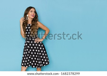 Happy beautiful young woman in black cocktail dress is holding hand on hip, looking away and talking. Three quarter length studio shot on blue background. Royalty-Free Stock Photo #1682378299