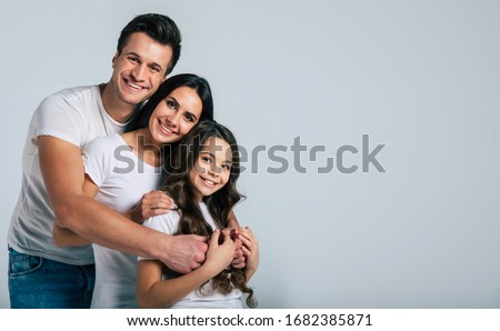 Our life! Beautiful excited and the funny family team is posing in a white t-shirt while they isolated on white background in studio. #1682385871