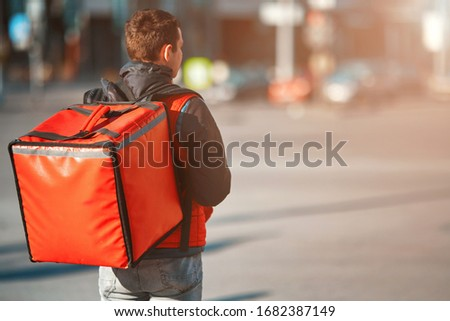 Сontactless food delivery to customers home. Delivery service worker with thermal backpack quick delivering food at doorstep in quarantine from restaurant, supermarket or cafe . Online ordering food #1682387149