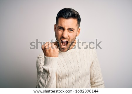 Young handsome man wearing casual sweater standing over isolated white background angry and mad raising fist frustrated and furious while shouting with anger. Rage and aggressive concept. Royalty-Free Stock Photo #1682398144