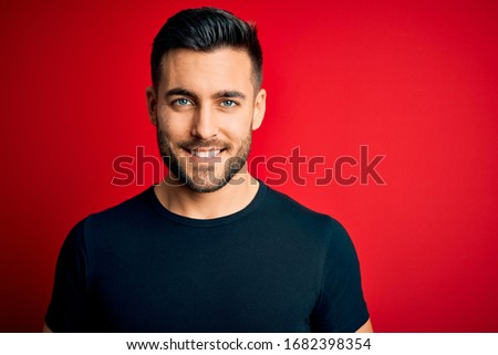 Young handsome man wearing casual black t-shirt standing over isolated red background with a happy and cool smile on face. Lucky person.