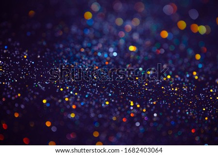 Decoration bokeh glitters background, abstract blurred backdrop with circles,modern design overlay with sparkling glimmers. Blue, purple and golden backdrop glittering sparks with glow effect