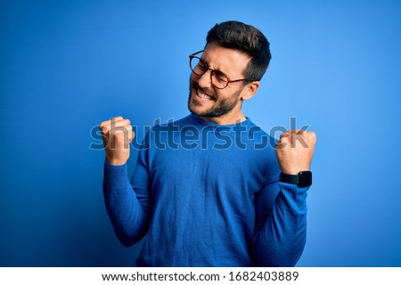 Young handsome man with beard wearing casual sweater and glasses over blue background very happy and excited doing winner gesture with arms raised, smiling and screaming for success. Celebration Royalty-Free Stock Photo #1682403889
