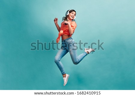 Young beautiful energy girl with white headphones listening to music laughs and jump on blue background in studio and looks away.Dressed in an orange shirt and light jeans, holding a phone. #1682410915