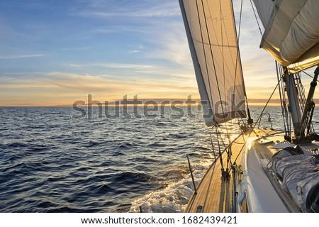 Sailboat sailing in the Mediterranean Sea at sunset Royalty-Free Stock Photo #1682439421
