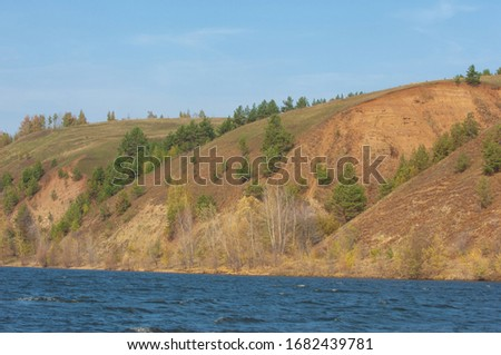 Autumn landscape, dark blue water, last warm days, river, trees, windy weather, yellow-red autumn leaves #1682439781