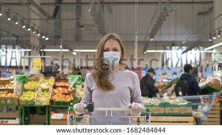 Woman with blond hair wearing a medical mask and rubber gloves stands with a grocery cart in a supermarket against the background of shelves with goods and customers. Protection from the coronavirus #1682484844