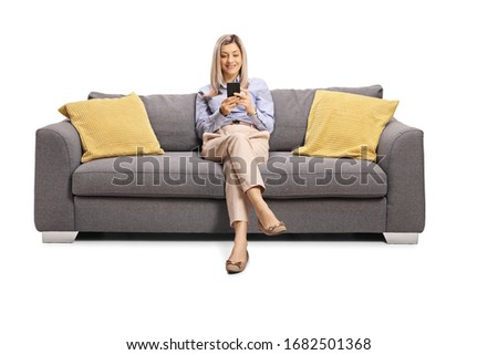 Woman resting on a sofa and holding a mobile phone isolated on white background #1682501368