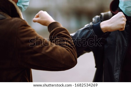 Friends in protective medical mask on his face greet their elbows in a quarantine city. Elbow bump is new greeting to avoid the spread of coronavirus. Don't shake hands. Stop handshakes. #1682534269