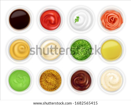 Many different sauces in round bowls set. Various ketchup mustard condiment in 3d realistic style. Top view. Textured pesto tartar spices isolated on white background. Oil, mayonnaise and sour cream Royalty-Free Stock Photo #1682565415