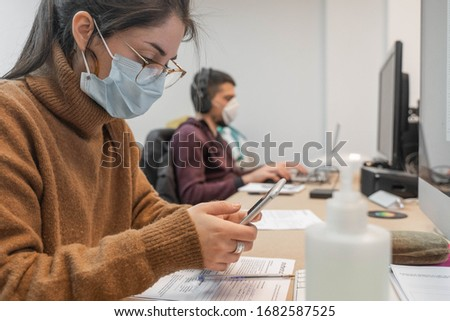 Coronavirus. Business workers working from home wearing protective mask. Small company in quarantine for coronavirus working from home with sanitizer gel. Small company concept. #1682587525