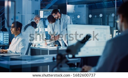 In Technology Research Laboratory: Diverse Team of Industrial Scientists, Engineers, Developers Gather Around Illuminated Table and Inspect Blueprints, Adjust 3D Printer, Choose Component Motherboard #1682600737