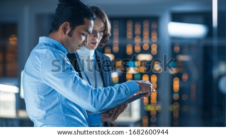 In Technology Research Facility: Female Project Manager Talks With Chief Engineer, they Consult Tablet Computer. Team of Industrial Engineers, Developers Work on Engine Design Using Computers Royalty-Free Stock Photo #1682600944