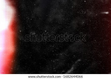 Designed film texture background with heavy grain, dust and a light leak Real Lens Flare Shot in Studio over Black Background. Easy to add as Overlay or Screen Filter over Photos overlay Royalty-Free Stock Photo #1682644066