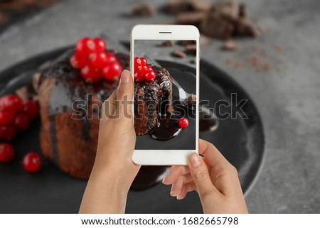 Food blogger taking picture of delicious warm chocolate lava cake at grey table, closeup