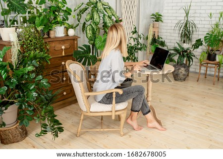Caucasian woman works on laptop in the home. Girl freelancer. Female in casual clothes. Online business. Remote job. Modern lifestyle, business day. Light workspace. Mobile device. Typing on keyboard #1682678005