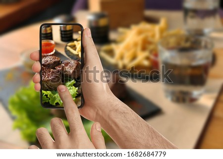 Food blogger taking picture of delicious shish kebab at table, closeup