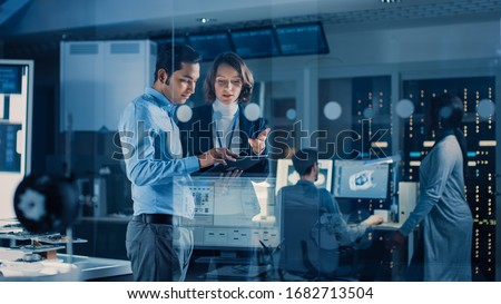 In Technology Research Facility: Female Project Manager Talks With Chief Engineer, they Consult Tablet Computer. Team of Industrial Engineers, Developers Work on Engine Design Using Computers #1682713504