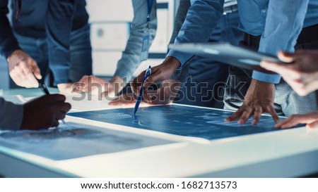 Engineer, Scientists and Developers Gathered Around Illuminated Conference Table in Technology Research Center, Talking, Finding Solution and Analysing Industrial Engine Design. Close-up Hands Shot #1682713573