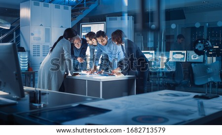 Engineers Meeting in Technology Research Laboratory: Engineers, Scientists and Developers Gathered Around Illuminated Conference Table, Talking and Finding Solution Inspecting Industrial Engine Design #1682713579