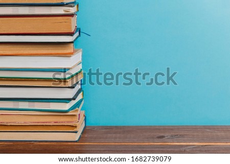 A simple composition of many hardback books, raw books on a wooden table and a bright blue background. back to school. Education. #1682739079