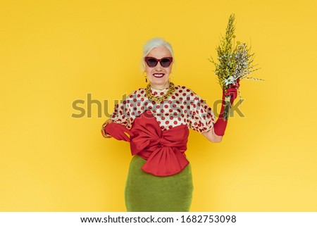 Stylish senior woman smiling while holding bouquet of wildflowers isolated on yellow #1682753098