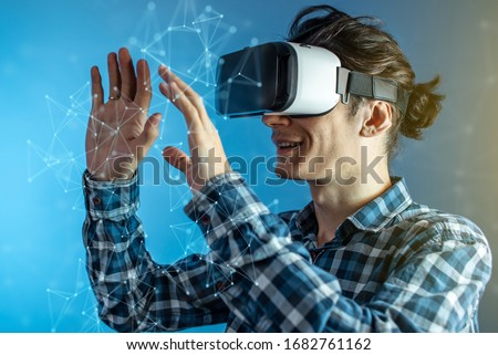 A young man wearing virtual reality glasses watching at a 3D visualization in an abstract polygonal grid on a blue background in a futuristic style. #1682761162