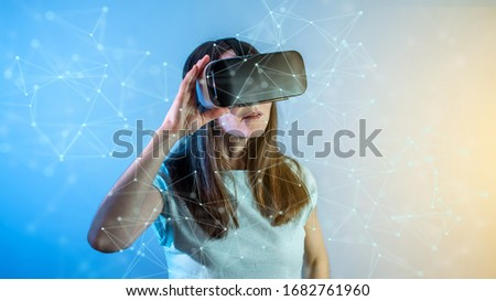 A young woman wearing virtual reality glasses watching at a 3D visualization in an abstract polygonal grid on a blue background in a futuristic style.