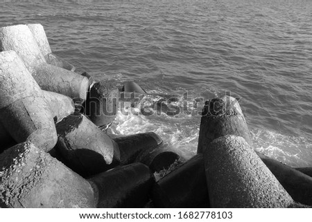 Breakwater stones on mole at Black sea in black and white. Sea view and background. #1682778103