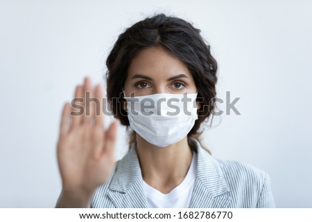 Portrait of young woman wearing medical protective mask show hand gesture to stop coronavirus pandemic, female in face cover stand against covid-19 virus outbreak, healthcare, epidemic concept #1682786770