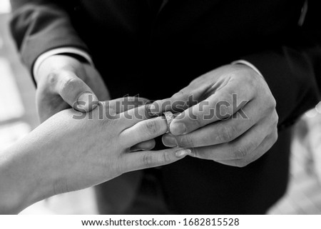 groom puts bride on wedding ring #1682815528