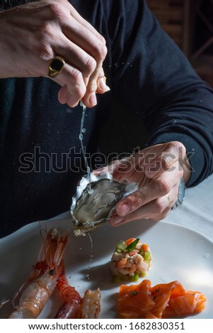 man eating raw oyster and shrimp #1682830351