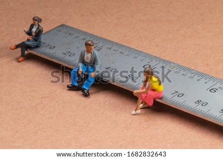 Miniature figures sit on a metal rule or ruler demonstrating the concept of social distancing to avoid transmission of the corona virus or other contagious illness #1682832643