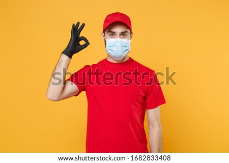 Delivery man in red cap blank t-shirt uniform sterile face mask gloves isolated on yellow background studio Guy employee working courier Service quarantine pandemic coronavirus virus concept #1682833408