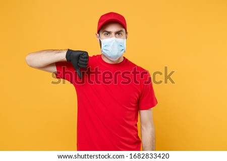 Delivery man in red cap blank t-shirt uniform sterile face mask gloves isolated on yellow background studio Guy employee working courier Service quarantine pandemic coronavirus virus concept #1682833420