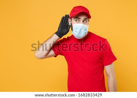 Delivery man in red cap blank t-shirt uniform sterile face mask gloves isolated on yellow background studio Guy employee working courier Service quarantine pandemic coronavirus virus concept #1682833429